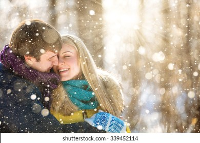 A loving couple walking in winter park. The snowfall