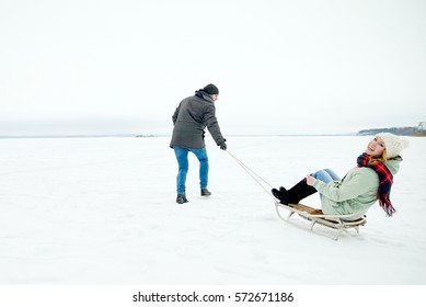 loving couple walks on the frozen, sledding