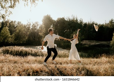 Loving couple walks and runs at sunset in the summer on the nature. Brunette girl in a hat and a light dress. Love story.