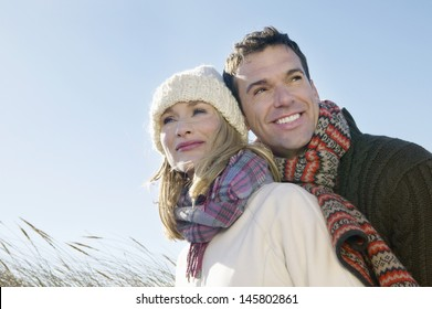 Loving couple in warm clothing embracing outdoors