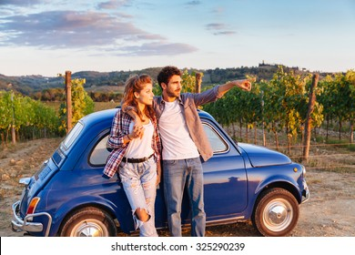A loving couple watch the sunset, standing leaning against an old blue car in Tuscany, Italy. Around them, rows of vines and the classic hills. The young man shows to his girlfriend sunset