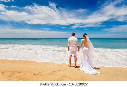 loving couple in wedding clothes stand  on the tropical beach, to hold hands