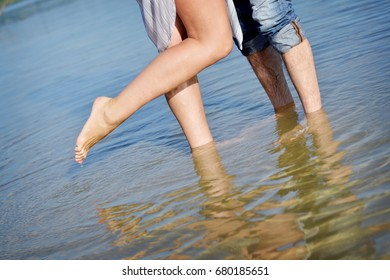 Loving couple, white caucasian girl and man, walking at the sea. Closeup view of legs and feet
