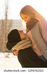 Loving couple in winter. The guy raises a girl in his arms on the street in winter. St. Valentine's Day
