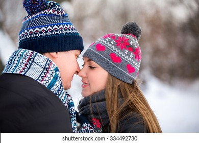 Loving couple in the winter park. People dressed in colorful hats and scarves.