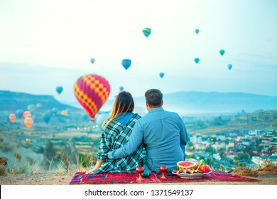 Loving couple, woman and man watching like colorful hot air balloons flying over the valley at Cappadocia, Turkey. Happy young couple during sunrise watching the hot air balloons of Kapadokya.