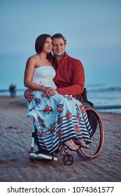 Loving couple, a woman sits on her husband's lap, resting on a beach against a background of a bright dawn.