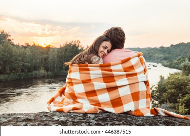 Loving couple wrapped in plaid sitting on mountain outdoors on sunset. Rear view. Man and woman traveling together. Traveler couple enjoying nature, embracing, watching landscape under a blanket.