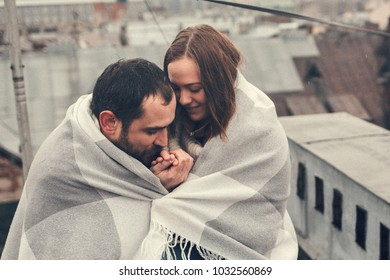 A loving couple, wrapping in a blanket, laughing and having romantic moments on roofs of Saint-Petersburg, Russia. Image with selective focus, noise effect and toning.