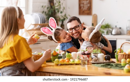Loving cute children wearing funny bunny ears headbands embracing and kissing cheerful young father while gathering with family at table in kitchen for Easter eggs painting