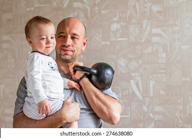 Loving dad with his son and kettlebell in hands