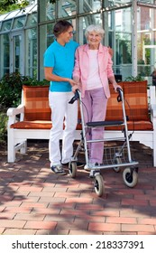 Loving daughter or care assistant helping her elderly mother as they enjoy a sunny day in the garden taking a walk with the use of a walking aid