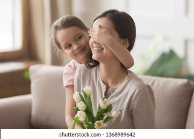 Loving daughter closing mum eyes making birthday surprise, happy excited mom receive white tulips bunch present from adorable girl, life events, mother day international womens day celebration concept