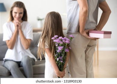 Loving daughter and grandmother preparing surprise for mother, standing with box and flowers in hands behind back, congratulating with birthday or mothers day, happy family party, multi generational