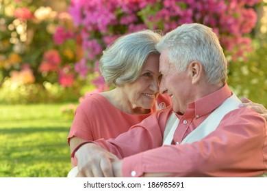 Loving elder couple sitting on a background of flowers