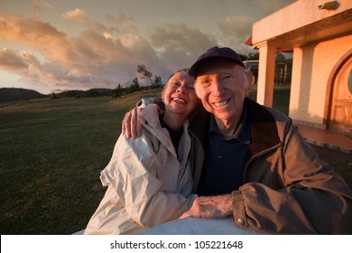 Loving elderly couple smiling at table in mountains