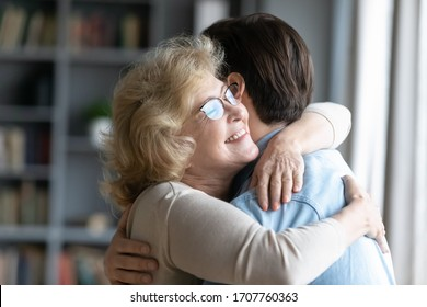 Loving elderly mother in glasses closed eyes enjoy moment strong cuddles adult son after long separation, grandmother glad to see grandson multi generational family reunion, love and bonding concept