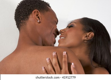 Loving ethnic black African-American young affectionate nude heterosexual couple in affectionate sensual kiss