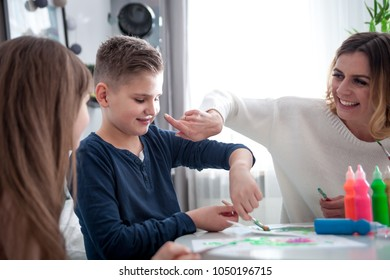 Loving family, mother with children together paint at home