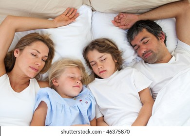 Loving family sleeping together lying in the bed