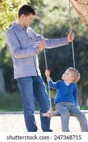loving family of two having fun swinging in the park