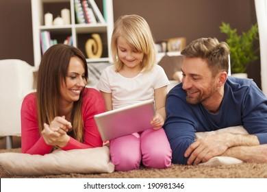 Loving family using digital tablet on carpet