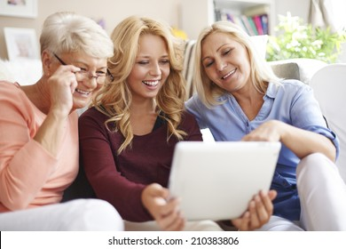 Loving family of women using digital tablet
