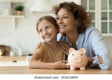 Loving family of young mother little daughter hug by kitchen table hold cute piggybank look away plan happy future life. Dreamy mom small child saving money for future vacation getting good education
