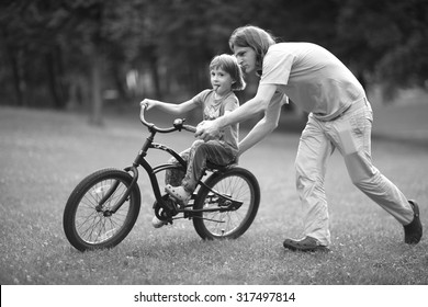 Loving father assisting his child riding a bicycle