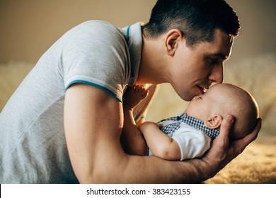 Loving father hand holding cute sleeping newborn baby child