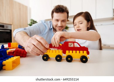 Loving father and his little daughter assembling construction set