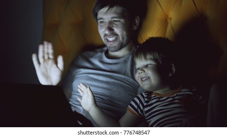 Loving father and his little son having online video chat with grandparents using tablet computer and while lying in bed in evening at home