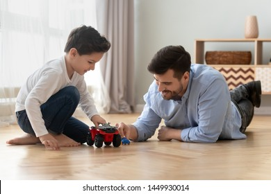 Loving father and little son playing toy cars, spending weekend together, having fun, engaged in game, caring dad and preschool child boy sitting on warm floor at home, underfloor heating concept