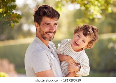 Loving Father With Son Having Fun In Park Holding Him In The Air Against Leafy Background