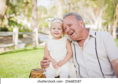 Loving Grandfather and Granddaughter Hugging Outside At The Park.