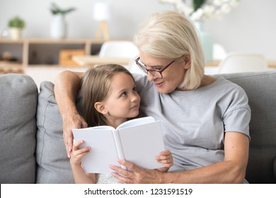 Loving grandmother teaching granddaughter holding book sitting on sofa, grandma baby sitter embracing kid girl reading fairytale to cute child, nanny granny telling story to preschool grandchild