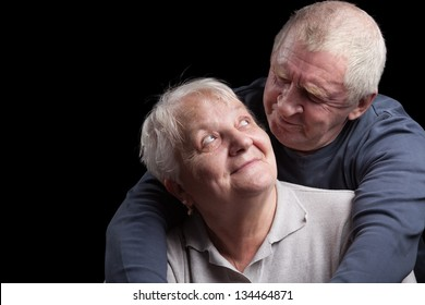 A loving, handsome senior couple on a black background.