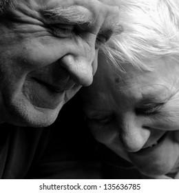 A loving, handsome senior couple on a black background.