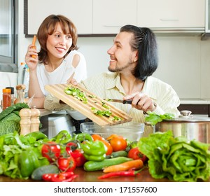 Loving happy couple cooking veggy lunch