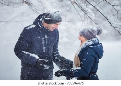 Loving happy couple walking in winter park. The snowfall