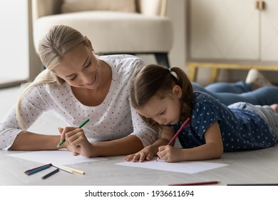 Loving happy young Caucasian mom and little daughter lying on floor drawing in album together. Caring smiling mother and small girl child have fun relax paining, involved in artistic activity.