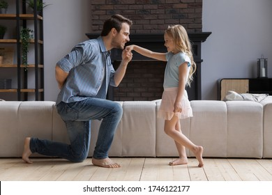 Loving happy young father kneel kiss little princess daughter hand play in living room together, overjoyed dad have fun engaged in funny girly game activity with overjoyed small preschooler girl child