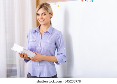 Loving her job. Young attractive female teacher is smiling brightly while standing near the whiteboard and holding papers.