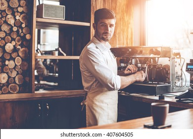 Loving his job. Young man in apron making coffee and looking at camera while standing at cafe