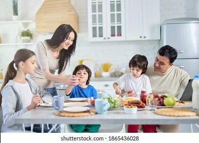 Loving hispanic parents taking care of their little children, entertaining them while having lunch together at home