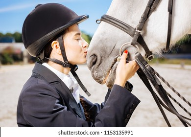 Loving horsewoman. Loving professional horsewoman with red nail art kissing her beautiful white horse