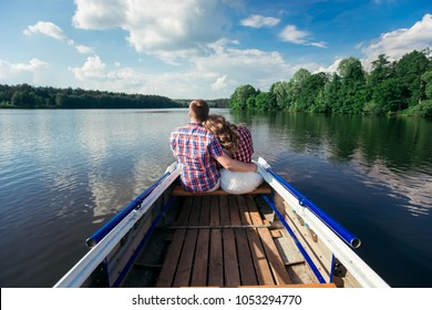 Loving hugging couple sits on the bow of the boat, and looks out into the distance to the forest