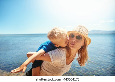 Loving little boy riding piggy back leaning forwards from behind and kissing his mother in a tender moment on a hot summer beach