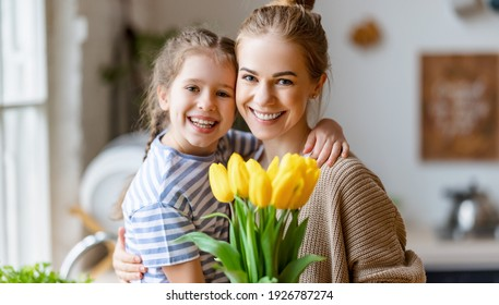 Loving little daughter hugging happy mom and greeting with bouquet of yellow tulips during Mothers day celebration at home