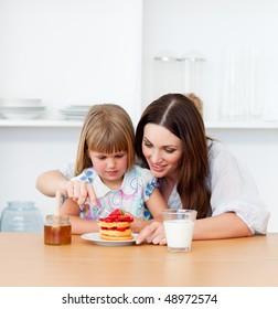 Loving little girl and her mother having breakfast in the kitchen